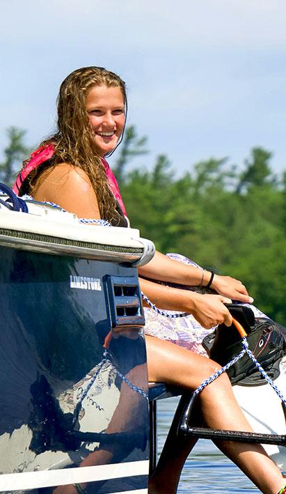 woman water skiing on back of limestone boat